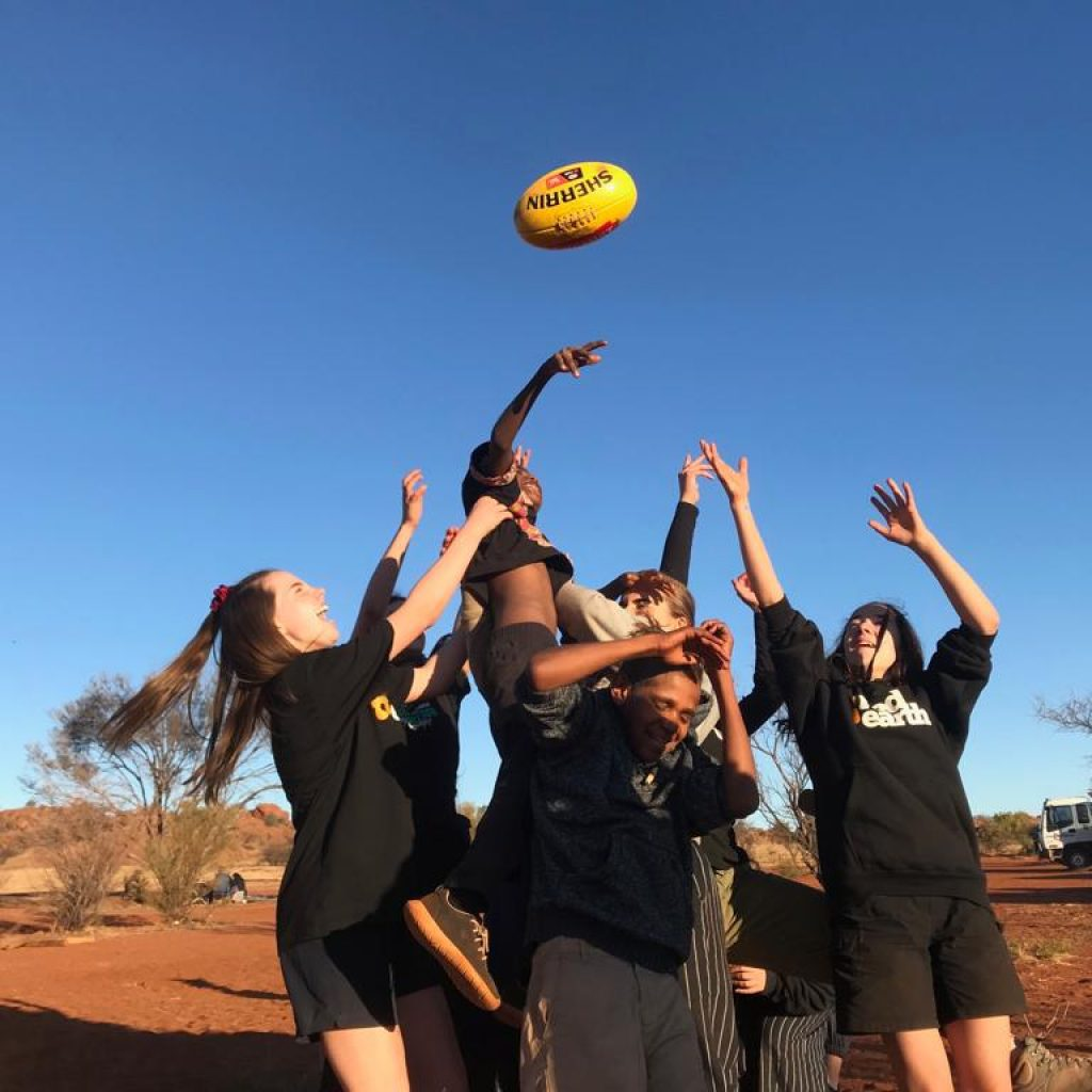 Santa Maria students playing footy with local kids on Red Earth Indigenous Cultural Immersion in Central Australia